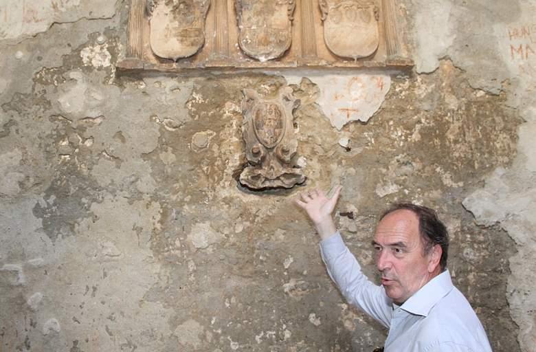 Josip Belamarić pokazuje mletački grb čija kojeg je nepoznati počititelj oštetio pokušavajući ga skinuti zajedno s kamenim blokom u koji je ukleasan (Foto H. Pavić)
