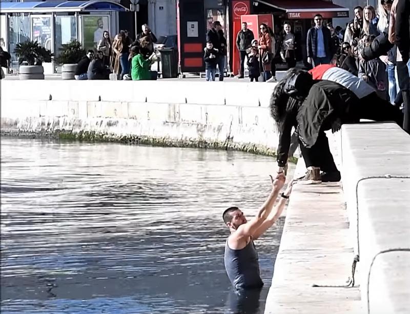 Trenutak u kojem djevojka i jedan stariji muškarac pomažu vaterpolistu da izađe iz mora (foto printscreen Youtube Slobodna Dalmacija)